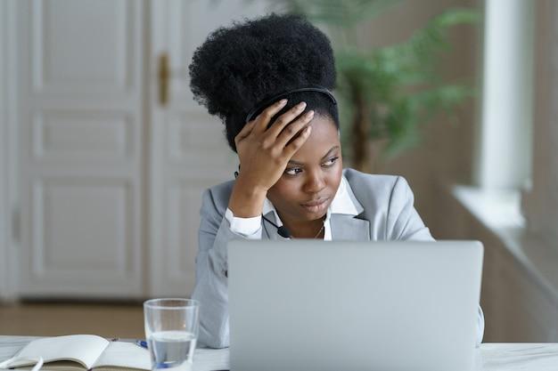 화난 원격 작업자 아프리카 여성 피곤한 착용 헤드폰은 우울한 고객과 의사 소통합니다.
