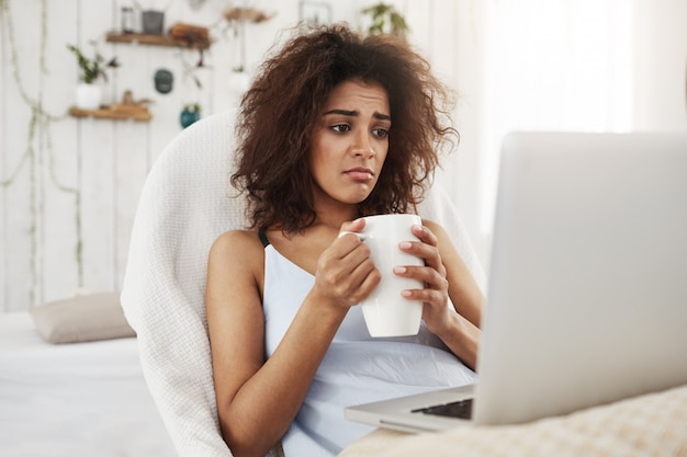 Upset sad beautiful african woman looking at laptop holding cup sitting in chair at home spending her weekend alone.