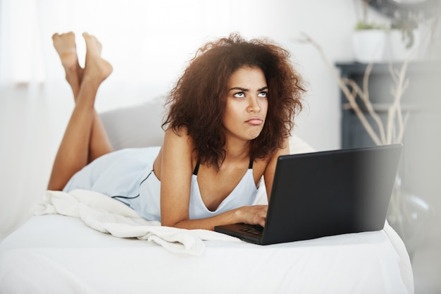 Upset sad beautiful african woman in sleepwear lying with laptop on bed at home thinking.