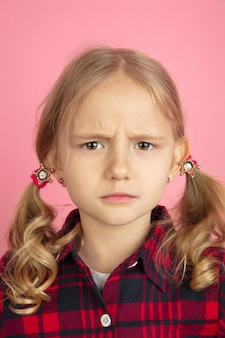 Upset, sad. caucasian little girl's close up portrait on pink wall. beautiful female model with blonde hair. concept of human emotions, facial expression, sales, ad, youth, childhood.