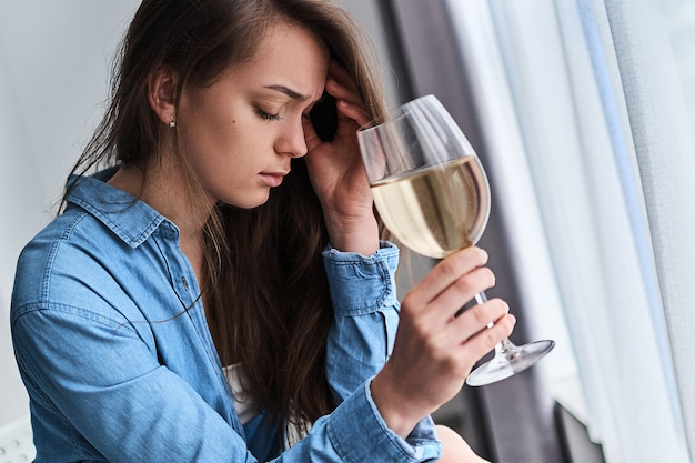 Расстроенная грустная подавленная подчеркнутая пьющая женщина с бокалом страдает от похмелья и головной боли. женский алкоголизм и жизненные проблемы, алкогольная зависимость при депрессии и переживаниях