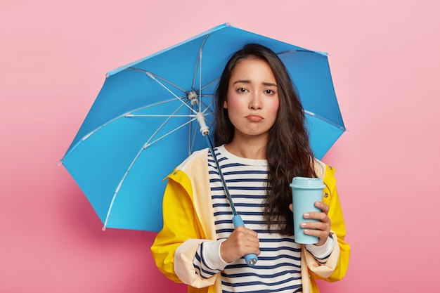 Upset sad korean girl walks under umbrella on rainy fall, drinks takeout coffee, dressed in waterproof raincoat