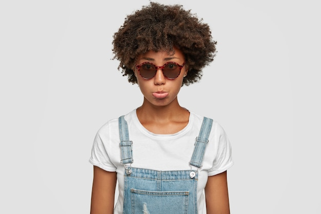 Upset sad young african american female purses lower lip, feels abused, wears fashionable round sunglasses and denim overalls, poses against white wall. people, emotions and style concept