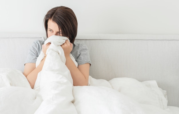 Upset sad young brunette woman sitting in bed at home, with copy space