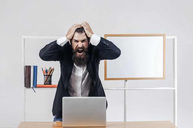 Upset screaming teacher or professor in black suit shouts raised his finger up standing near desk with laptop