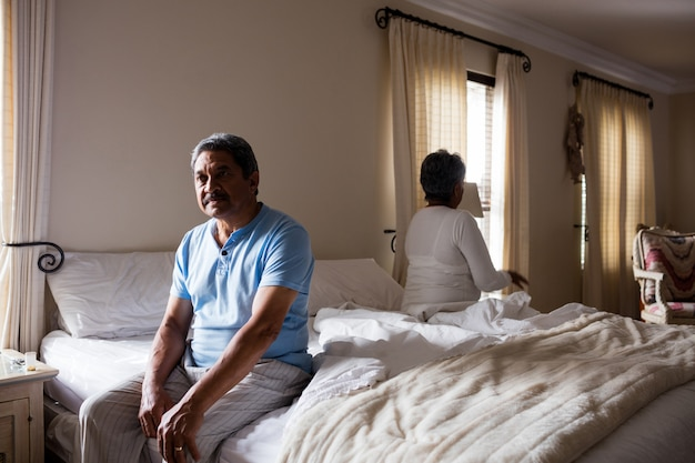 Upset senior couple ignoring each other in bedroom