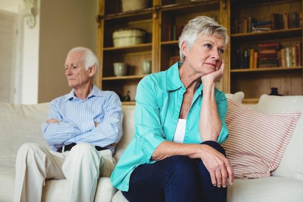 Upset senior couple ignoring each other in living room
