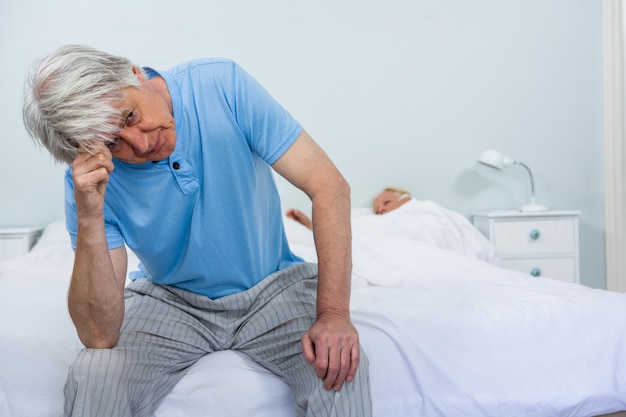 Upset senior man touching head while woman sleeping on bed