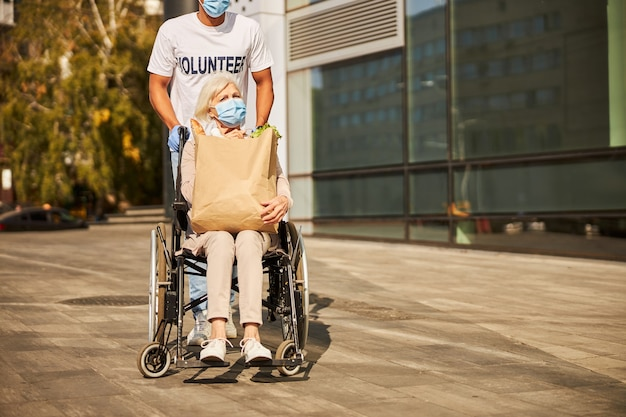 Upset senior woman sitting in a wheelchair and holding a groceries package on her knees