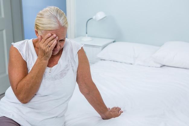 Upset senior woman touching head at home