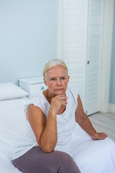 Upset senior woman with hand on chin sitting on bed
