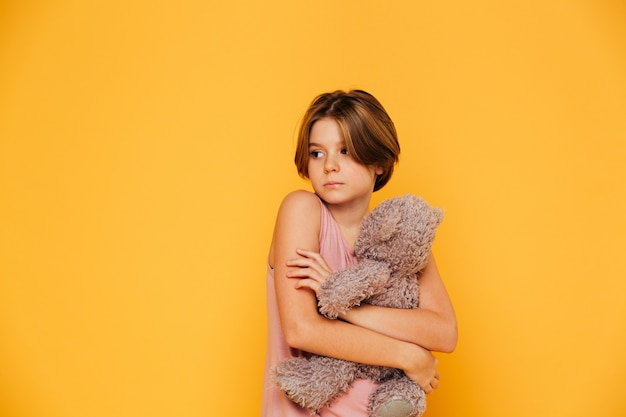 Upset serious girl holding her bear hard and looking aside isolated
