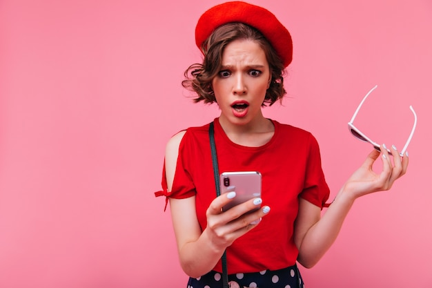 Upset short-haired girl reading phone message. indoor photo of surprised french female model in beret posing with mouth open.