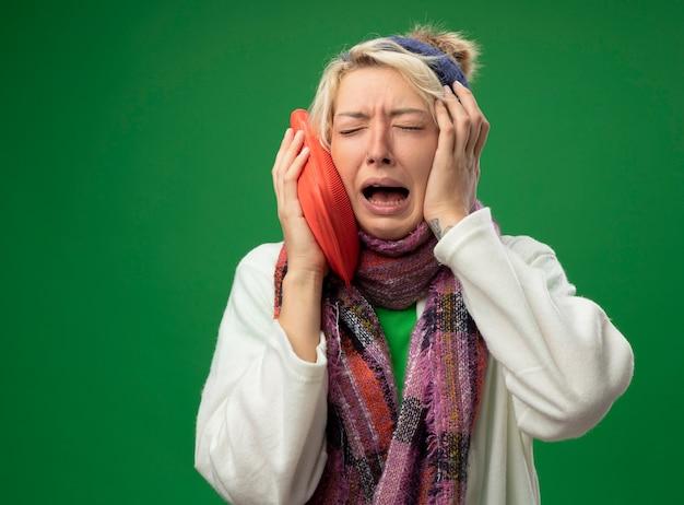 따뜻한 스카프와 모자에 짧은 머리를 가진 아픈 건강에 해로운 여자를 화나게하고 녹색 배경 위에 서있는 독감으로 고통받는 따뜻한 울음에 물병을 들고 기분이 좋지 않습니다.