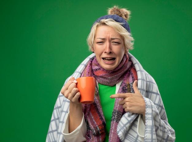 Расстроенная больная нездоровая женщина с короткими волосами в теплом шарфе и шляпе чувствует себя нездоровой, завернувшись в одеяло, держит чашку чая, указывая на нее указательным пальцем, плачет, стоя на зеленом фоне