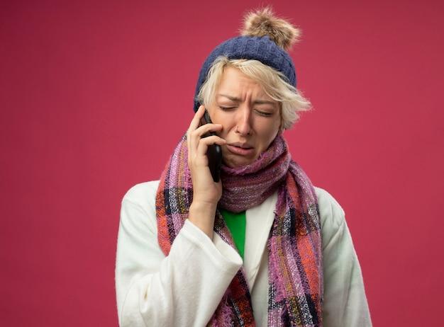Donna malsana malata sconvolta con capelli corti in sciarpa calda e cappello sensazione di malessere piangere mentre parla al telefono cellulare in piedi sopra il muro rosa