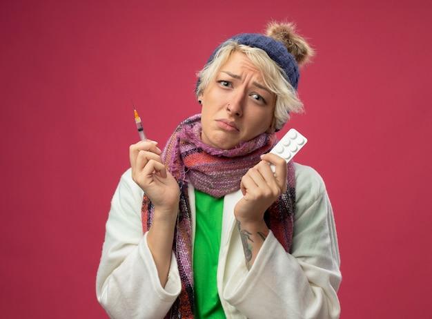 Donna malsana malata sconvolta con capelli corti in sciarpa calda e cappello sensazione di malessere tenendo la medicina e la siringa guardando la telecamera in piedi su sfondo rosa
