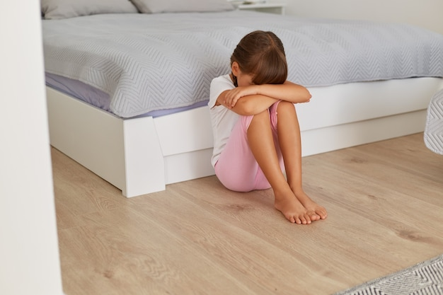 Upset small child girl crying sitting alone on floor, sitting near bed with her head down, sad lonely kid being bullied abused, feeling stressed or scared, children violence.
