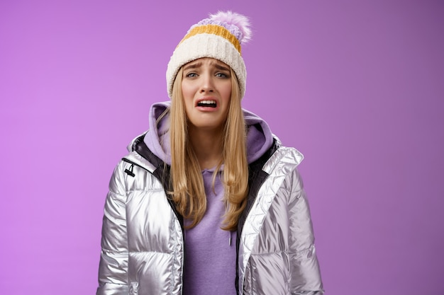 Upset sobbing miserable cute blond woman in silver stylish jacket hat crying whining unhappy feel sadness distress look disappointed complaining cruel life, unlucky standing purple background.