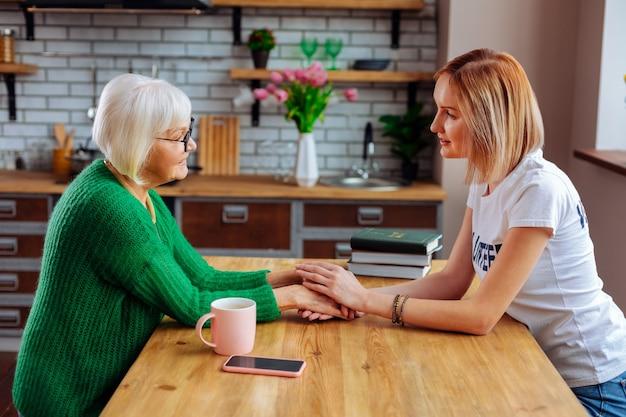 흰색 티셔츠에 젊은 금발 아가씨와 이야기하면서 감정을 표현하는 짧은 회색 머리를 가진 슬픈 연금 수령자 프리미엄 사진