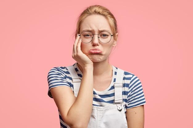 Расстроенная грустная женщина сожалеет о ссоре с близким человеком, портит нижнюю губу, имеет здоровую кожу, светлые волосы, носит повседневную футболку