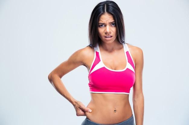Расстроенная спортивная женщина трогает жир на животе