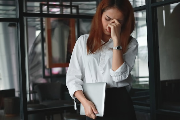 Upset stressed asian business woman standing in office.