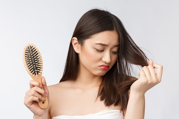 Upset stressed young asian woman holding damaged dry hair on hands over white isolated wall