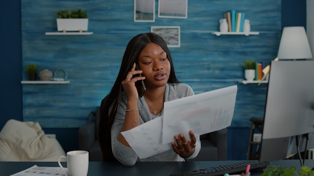 Studente sconvolto seduto al tavolo della scrivania in soggiorno che spiega i compiti della scuola superiore discutendo con un collega utilizzando lo smartphone