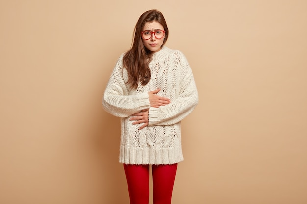 Upset sullen european female touches belly from pain, feels unwell, discomfort after eating spoiled product, wears spectacles and warm clothes, stands over brown wall. stomachache concept