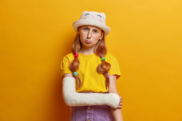 Upset sullen ginger girl broke arm during rolleblading, suffers from pain and fracture, wears cast, has bad mood, dressed in summer clothes, visited doctor, got into accident, has plastered hand