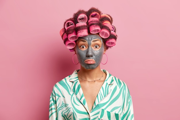 Upset surprised woman purses lips applies clay mask for skin rejuvenation makes perfect hairstyle wears silk dressing gown isolated over pink wall. face care and beauty procedures concept