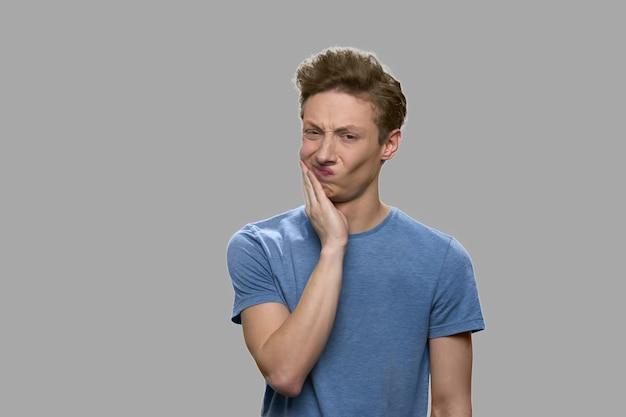 Расстроенный мальчик-подросток, имеющий зубную боль. эмоциональный подросток, страдающий от зубной боли, вид спереди.
