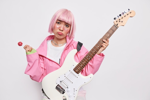 Upset teenage girl cannot learn playing guitar holds sweet lollipop bass acoustic guitar has pink hair with fringe tries to record music in studio peforms favorite songs
