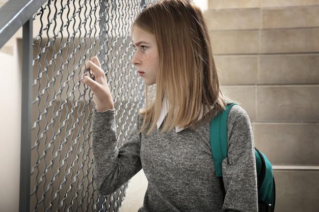 Расстроенная девочка-подросток с рюкзаком на лестнице в помещении
