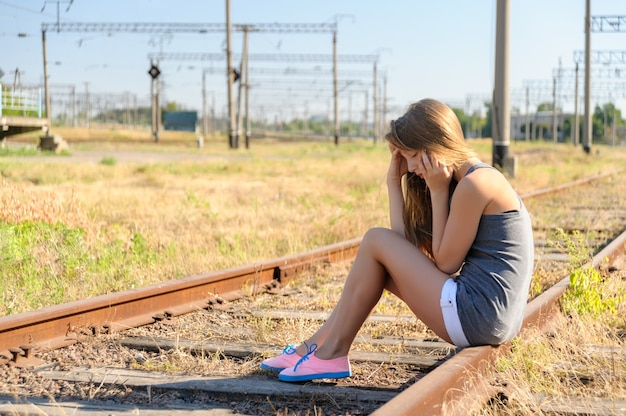 Upset teenager girl sitting on rail track in countryside