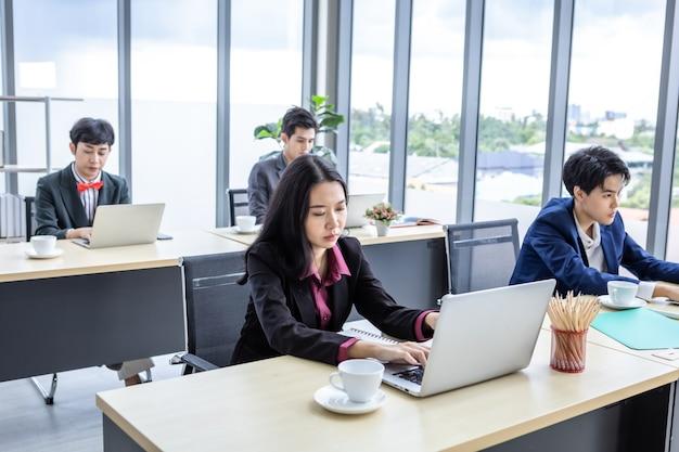 사려깊은 젊은 아시아 사업가 사무실 직원의 노트북 컴퓨터로 일하는 직장에서 스트레스를 받는 것은 사무실 뒤에 있는 동료들과 함께 하는 것에 만족하지 않습니다