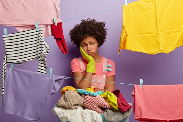 Upset tired afro woman busy with housework, wears rubber gloves, dries clothes, has much jobs around house, stands near basket of dirty linen, isolated over purple background.
