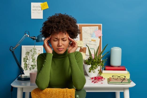 動揺した疲れた女性は、こめかみに両手を置き、顔を眉をひそめ、長時間働いた後、過労を感じます