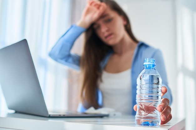 Upset tired working woman suffering from heat, thirst and hot weather cools down with cold water bottle during online work at computer at warm summer day