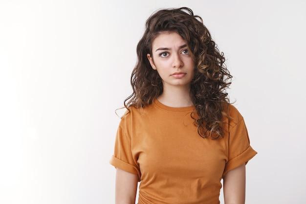 動揺して疲れた若いアルメニアの縮れ毛の女性は疲れ果てた感じ失望した侮辱されたカメラ暗い視線立っている白い背景は信仰を失う奇跡は起こり得ない、落ち込んで泣きたい