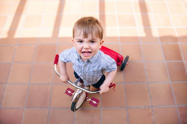 Расстроенный малыш, испытывающий трудности при езде на велосипеде дома.