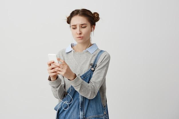 後悔の視線とすぼめた唇でスマートフォンを探している動揺のトレンディな女の子。ブルネットの女性は、アップロードしようとしているガジェットでお気に入りの音楽を見つけることができません。テクニクスのコンセプト