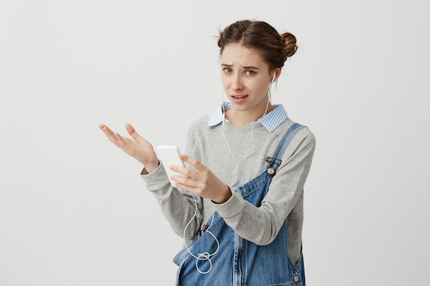 Upset trendy girl looking on smartphone with regret gaze and pursed lips. brunette woman can't find favourite music in her gadget trying to upload it. technics concept