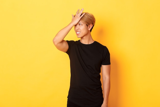Il ragazzo asiatico turbato e turbato schiocca la fronte smemorato, in piedi sopra il muro giallo