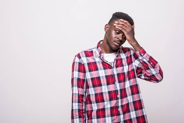 動揺して不幸なアフロアメリカンの男が手で頭を絞って、苦痛で身もだえ、頭痛に苦しんでいます。人、ストレス、緊張、片頭痛