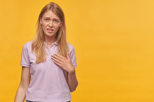 Upset unhappy blonde young woman with freckles in lavender tshirt feels embarrassed and points at herself over yellow wall