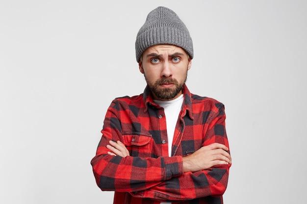 Расстроенный несчастный молодой человек над белой стеной