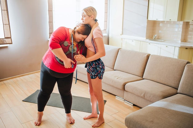 Upset unhappy young overweight woman leaning to slim model and crying.