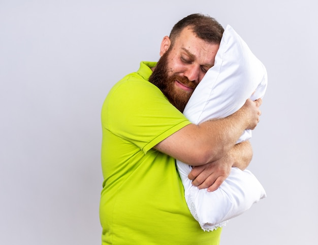 黄色いポロシャツを着た不健康なひげを生やした男が、枕を持って気分が悪く、白い壁の上に立って眠りたい
